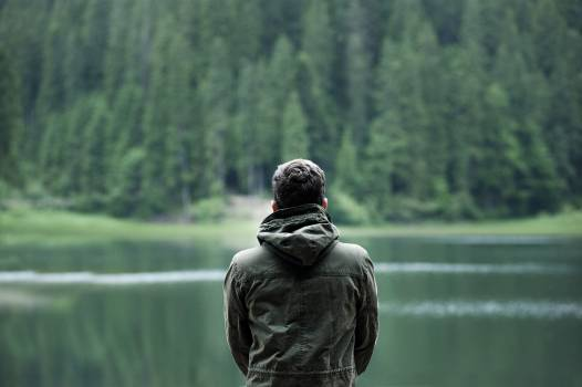 Photo of Man Wearing Hooded Jacket in Front of Body of Water #327751