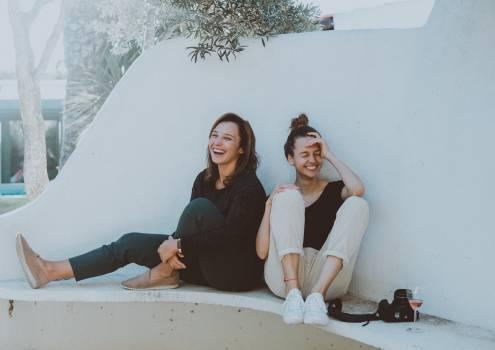 Two Women Sitting on White Bench Free Photo