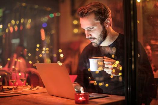 Man Holding Mug in Front of Laptop Free Photo