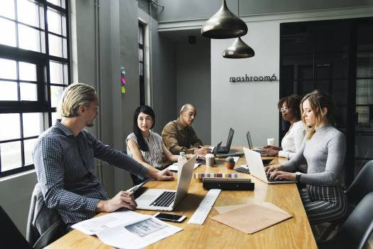 Five Person Sitting Front of Conference Table With Laptop Computers Free Photo