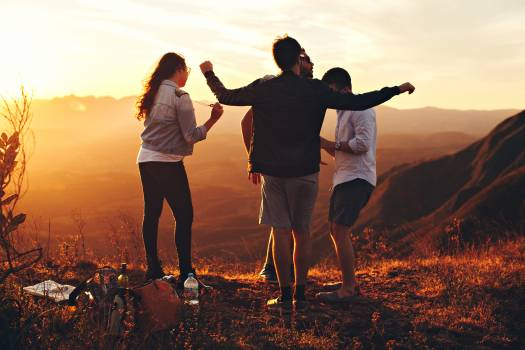 Four Person Standing at Top of Grassy Mountain Free Photo