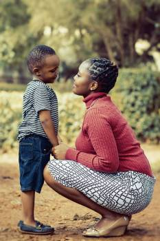 Tilt Shift Lens Photography of Woman Wearing Red Sweater and White Skirt While Holding a Boy Wearing White and Black Crew-neck Shirt and Blue Denim Short Free Photo