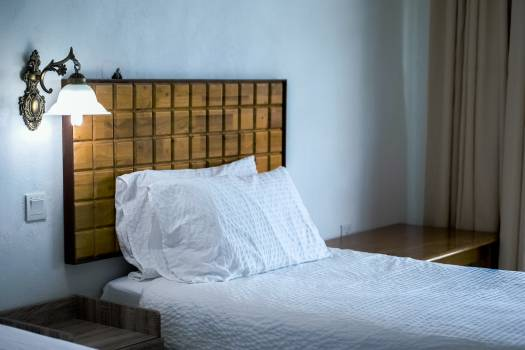 White Bedding Cover Beside Brown Wooden Side Table #32896