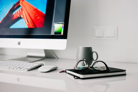 Silver Imac Turned on Beside Gray Ceramic Mug and Black Frame Eyeglasses #32907
