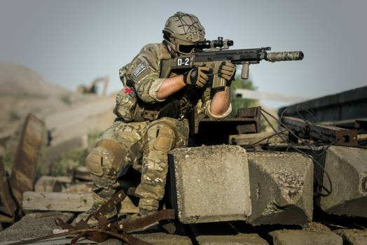 Soldier Near Concrete Pillars Holding Semi Automatic Gun With Scope #329440