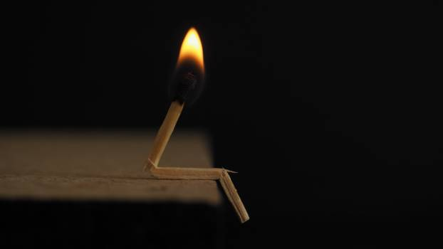 Lighted Matchstick on Brown Wooden Surface Free Photo