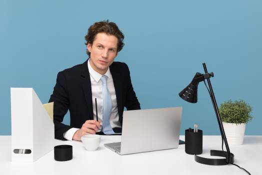 Man Sitting With Laptop Computer on Desk and Lamp Free Photo
