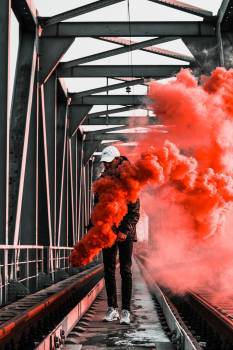 Man in Black Jacket Holding Red Smoke on Metal Bridge #329521