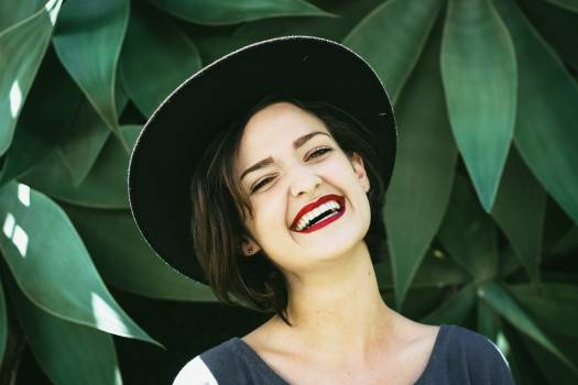 Woman Smiling In Front Of Green Plants Free Photo