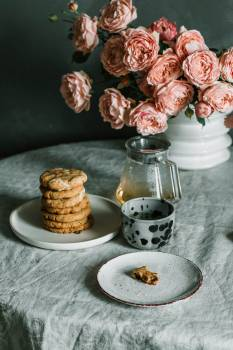 Pink Flowers Beside Plate of Biscuits Free Photo
