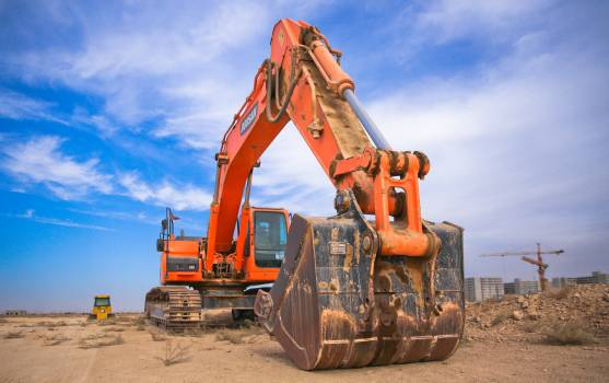 Low Angle Photography of Orange Excavator Under White Clouds Free Photo
