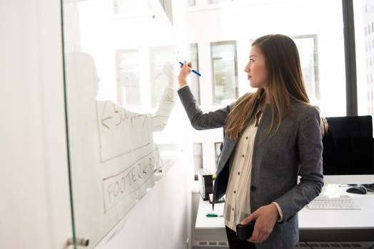 Woman Wearing Gray Blazer Writing on Dry-erase Board #329972