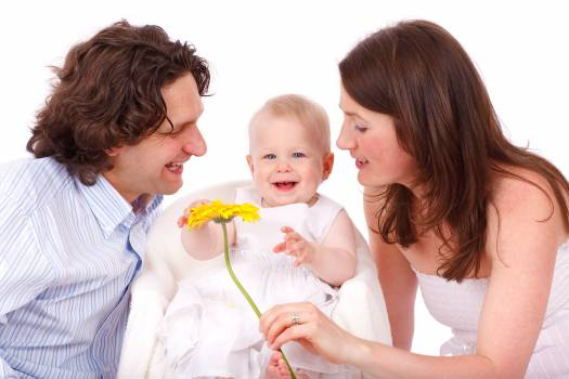 Man in White and Gray Stripe Button Up Long Sleeve Shirt Facing Baby in White Sleeveless Dress Beside Woman in White Strapless Dress Holding Yellow Flower #33071