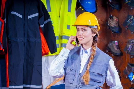 Woman in Gray Vest With Yellow Hard Hat Inside Room Free Photo