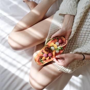 Person Holding Papaya Fruit on Bed Free Photo