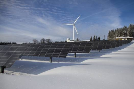 Solar Panels on Snow With Windmill Under Clear Day Sky Free Photo