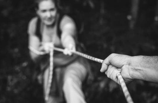 Grayscale Photo of Person Pulling Up Woman Using Rope Free Photo