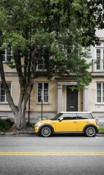 Yellow Mini Cooper Parked Beside White Concrete Building Free Photo