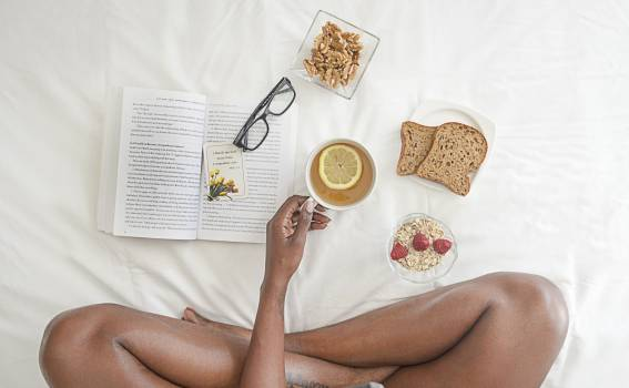Person Holding White Ceramic Mug With Lemon Near Book and Sliced Bread on White Comforter Free Photo