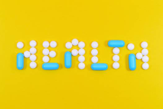 White and Blue Health Pill and Tablet Letter Cutout on Yellow Surface #332702