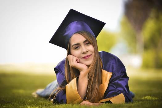 Woman Wearing Purple Graduation Gown Lying on Field Free Photo