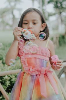 Girl Wearing Multicolored Dress Making Bubbles Free Photo