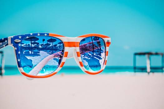 Focus Photography of American Flag-accent Wayfarer-styled Sunglasses With Sea Background Free Photo