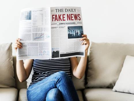 Person Reading the Daily Fake News Newspaper Sitting on Gray Couch #333442