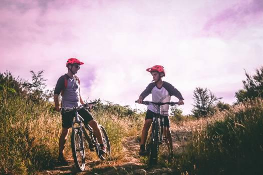 Two Man Riding Mountain Bike on Dirt Road at Daytime Free Photo