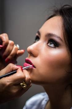 Woman Putting Lipstick on Her Lips Free Photo