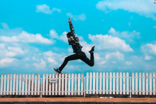 Man Jumping over White Fence Free Photo