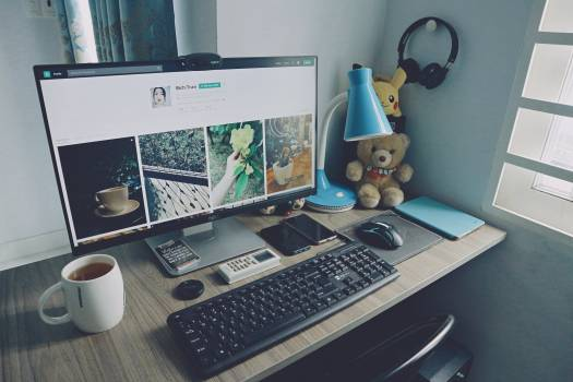 Turned on Monitor, Keyboard, and Items on Desk Free Photo