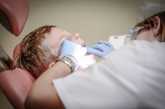 Dentist Woman Wearing White Gloves and White Scrubsuit Checking Boy's Teeth #33405