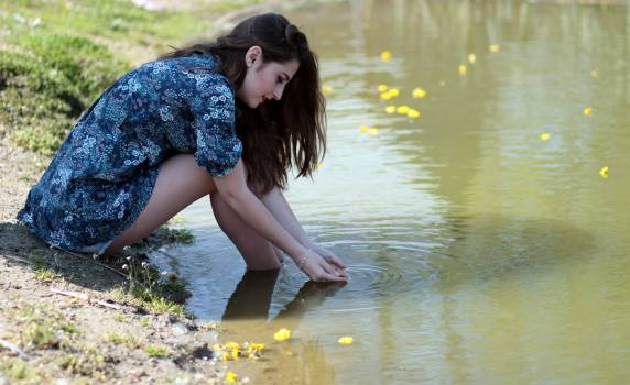 Woman Soaking Her Feet on Body of Water during Daytime #33425