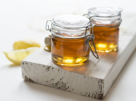 Two Clear Glass Jars of Oils on Wooden Plank #334322