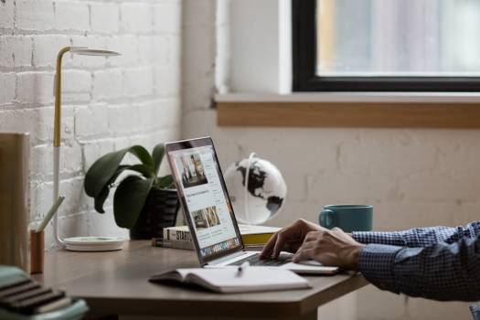 Man Sitting in Front of Turned-on Laptop on Brown Wooden Desk Free Photo