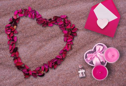 Pink Flower Petals and Pink Envelop on Top of Sand Free Photo