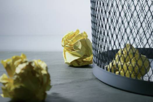 Focus Photo of Yellow Paper Near Trash Can #334458