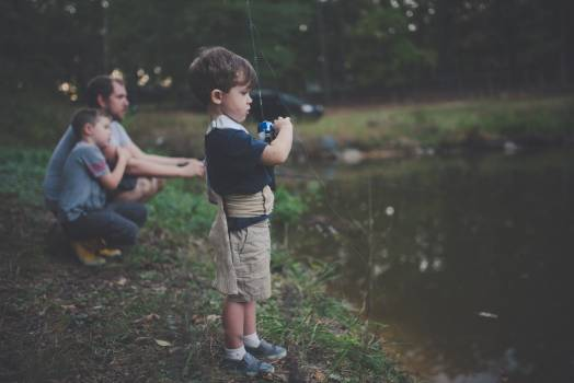 Child Holding Blue and Black Fishing Rod Beside Body of Water #33457