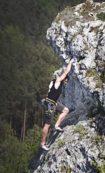 Man Wearing Black Tank Top and Brown Shorts Climbing Rock Free Photo
