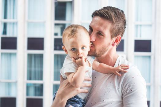 Man Holding and Kissing Baby Free Photo