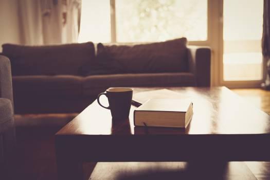 Black Ceramic Mug Beside Black Hardbound Book on Brown Wooden Coffee Table #33493