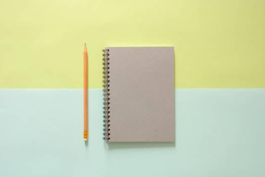 White Spiral Notebook Beside Orange Pencil Free Photo