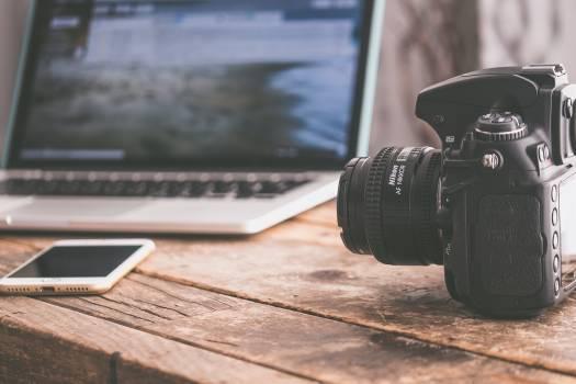 Black Dslr Camera on Beige Wooden Surface Free Photo