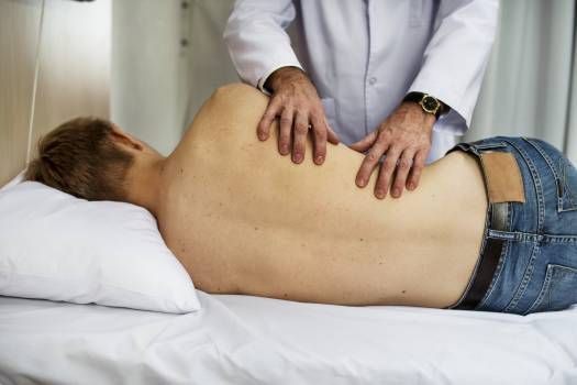 Person Massaging Man While Lying on Bed Free Photo