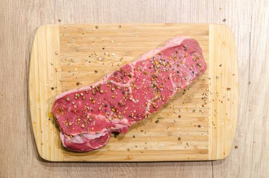 Flat Lay Photography of Slice of Meat on Top of Chopping Board Sprinkled With Ground Peppercorns Free Photo