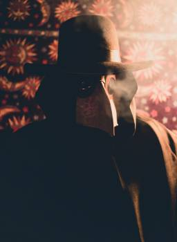 Person in Black Coat and Hat With Plague Doctor Mask Free Photo
