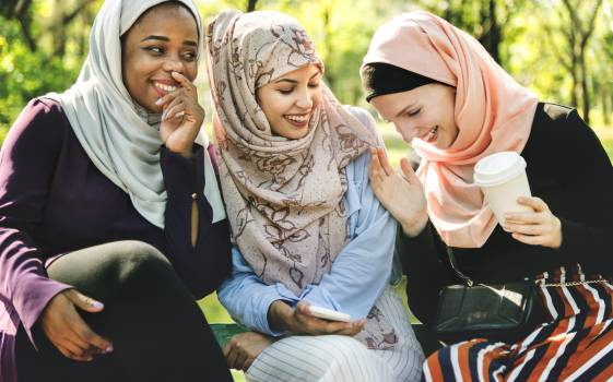 Photo of Women Laughing and Dressed in Hijabs Sitting Next to Each Other. Free Photo