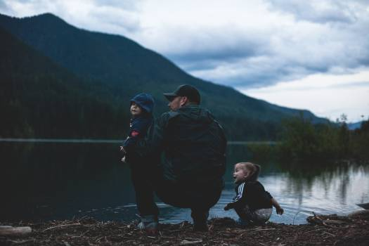 Man With Two Kids Near Body of Water Free Photo