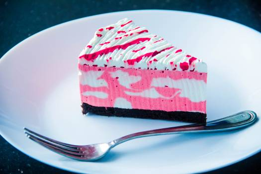 Sliced White and Pink Icing Covered Cake on White Plate With Silver-colored Fork #336632
